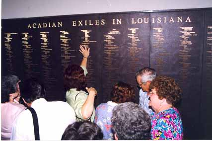 A visitor reaches to touch the name of her Acadian ancestor after the unveiling of the Wall of Names