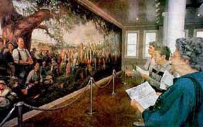 Standing in front of the mural, a Memorial docent recounts the history of the Acadians to visitors
