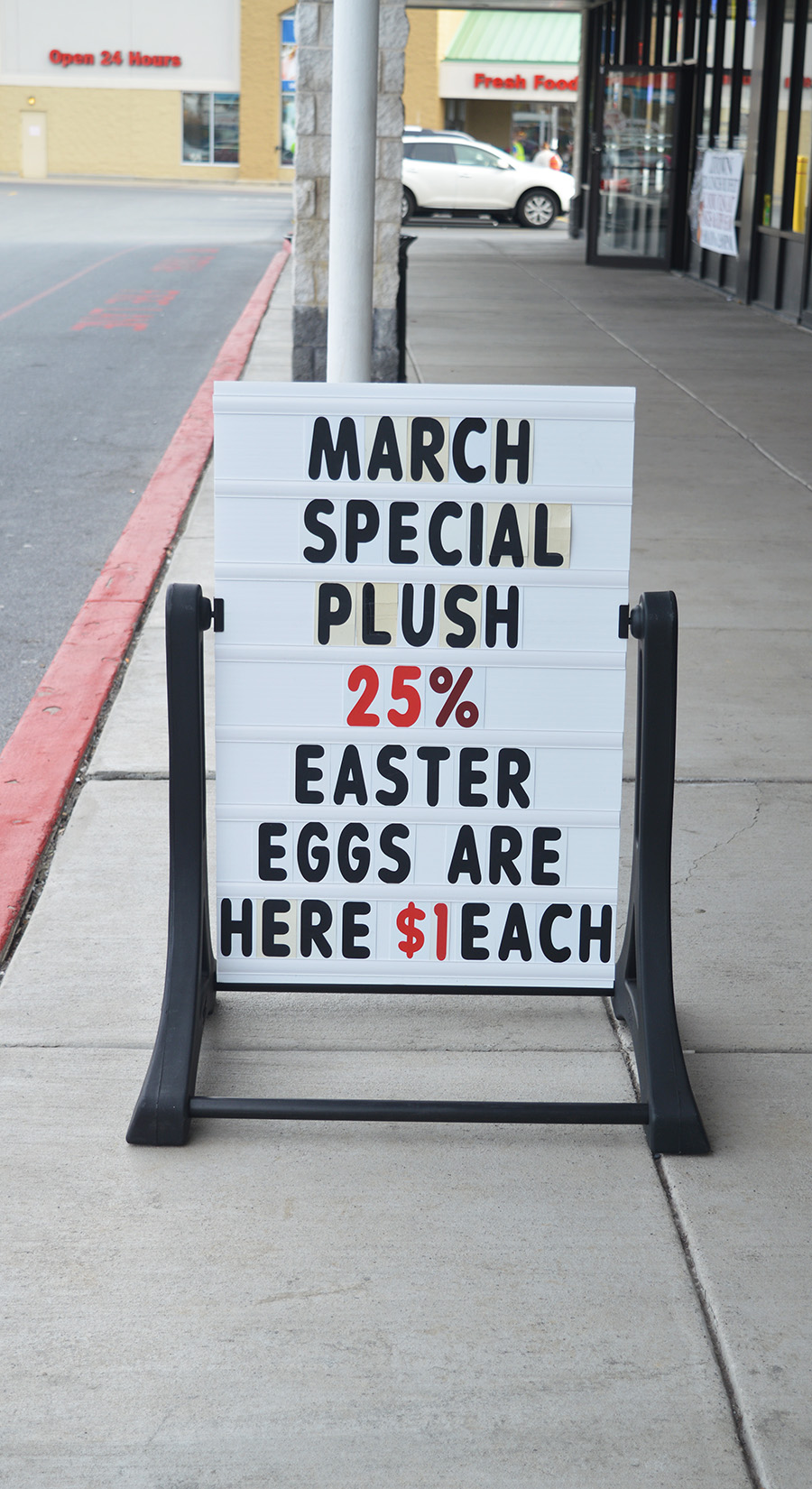 Sidewalk sign with large black letters announcing a March special of 25% off forchocolate Easter eggs, $1 each. Photo: Mira Johnson.