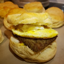 A square of homemade livermush, darkly browned, with a well-fried egg on top, all sandwiched between biscuit halves. Lenoir, NC, March 10, 2019. Photo: Paula Castleman.