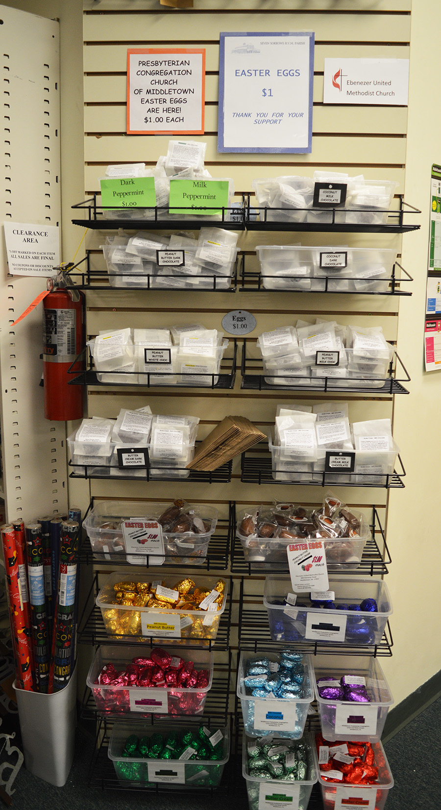 Middletown Pharmacy & Gifts seasonal wire rack wall display of chocolate eggs made by area church groups and variably presented in small labeled plastic bags or foil-wrapped in a spectrum of Easter colors. The top four rows are from Seven Sorrows Church, the middle row is from Presbyterian Congregation of Middletown Church. and the bottom three rows are from Ebenezer United Method Church. Each bin holds a different variety of chocolate egg. Middletown, March 12, 2016. Photo: Mira Johnson.