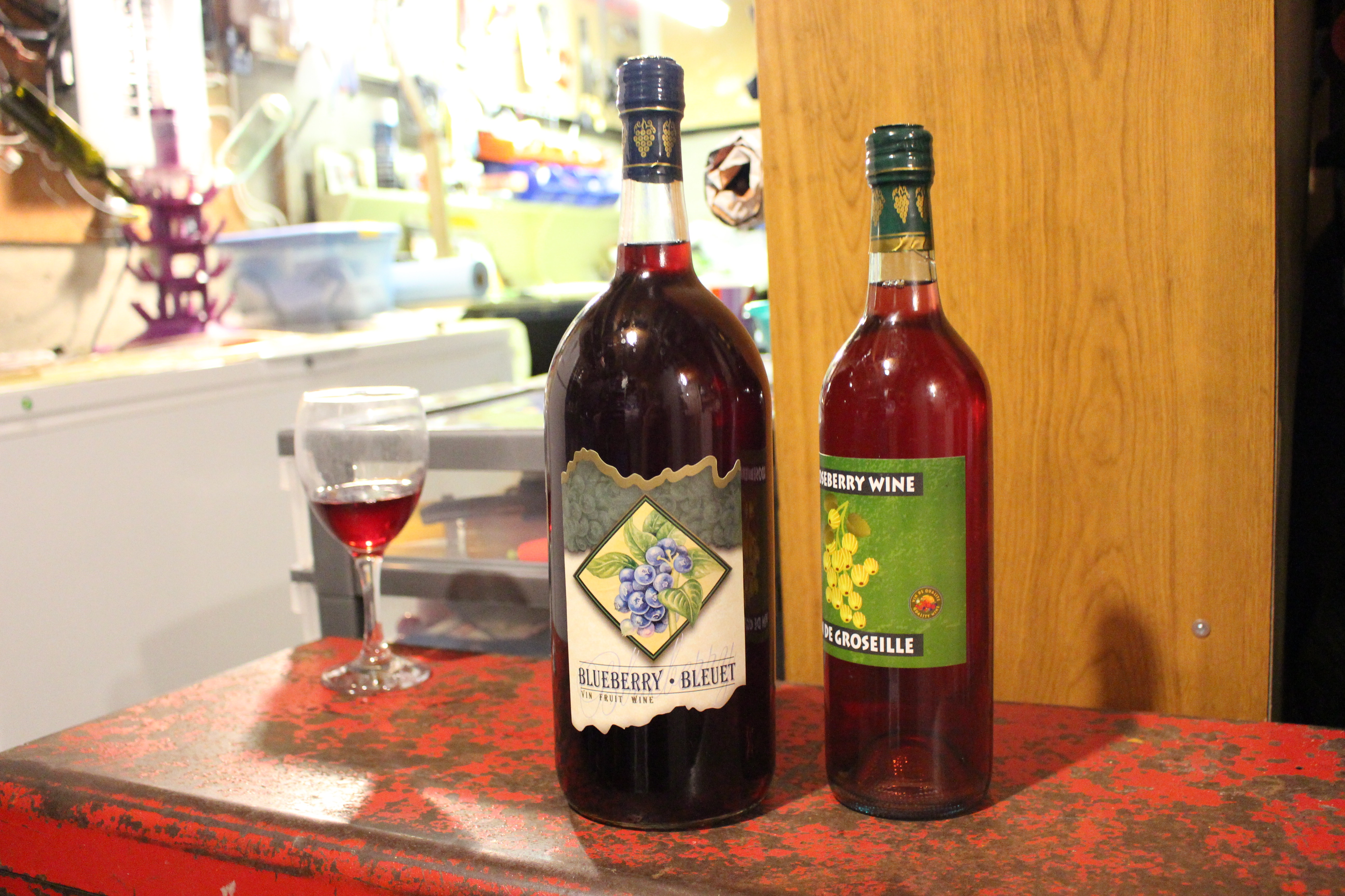One small-medium wineglass of gooseberry wine, a bottle of blueberry wine, and a bottle of gooseberry wine—all made by Herbert Greening and displayed along a horizontal surface in his basement wine-making area. The bottle labels feature both English and French and illustrations of a bunch of blueberries with leaves on one, and a sprig of yellow-green gooseberries on the other. Mount Pearl, Newfoundland, 9 November 2017. Photo: Ema Noëlla Kibirkstis.